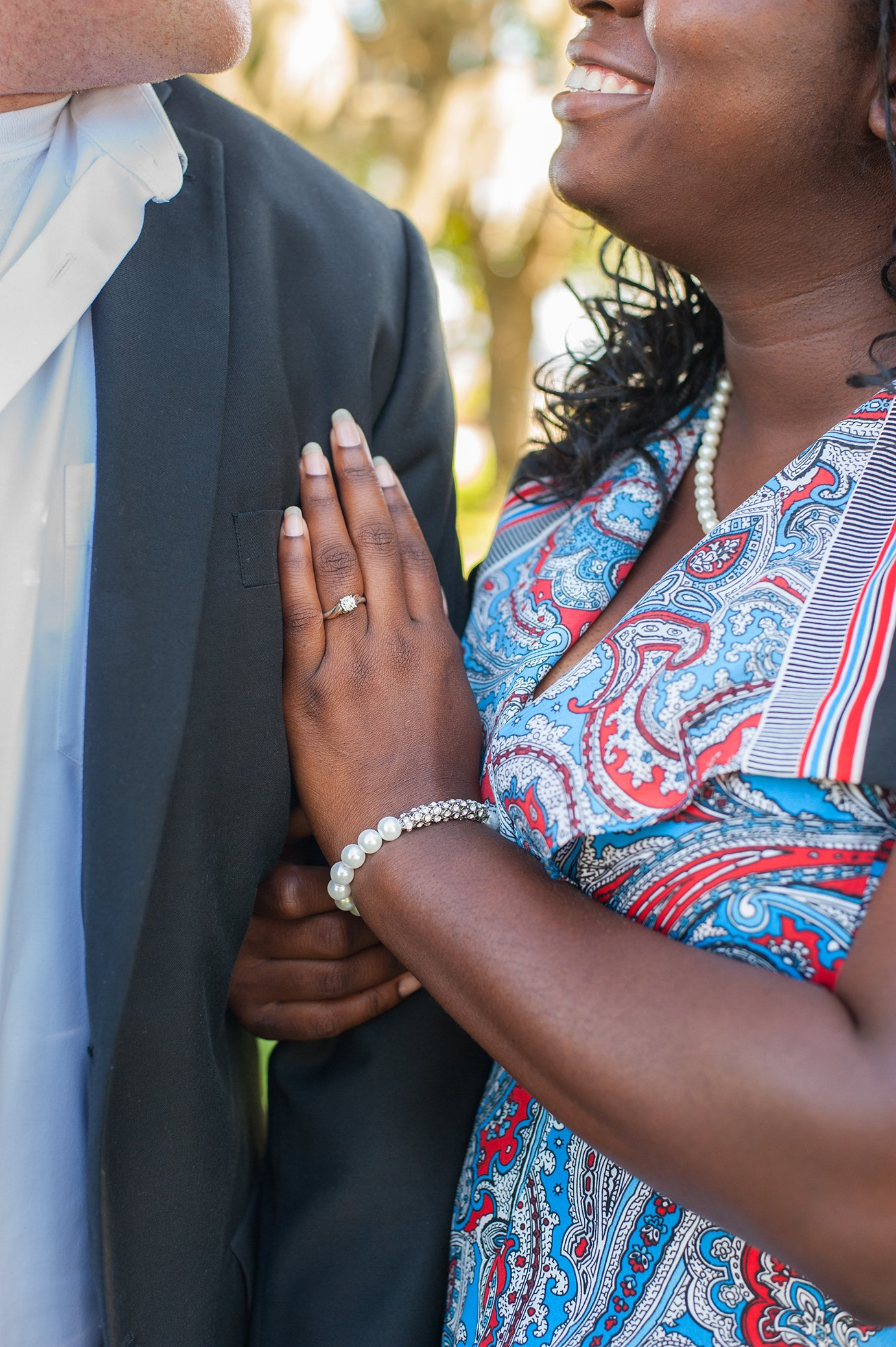 Engaged couple show off engagement ring in engagement photos at riverfront park in charleston sc