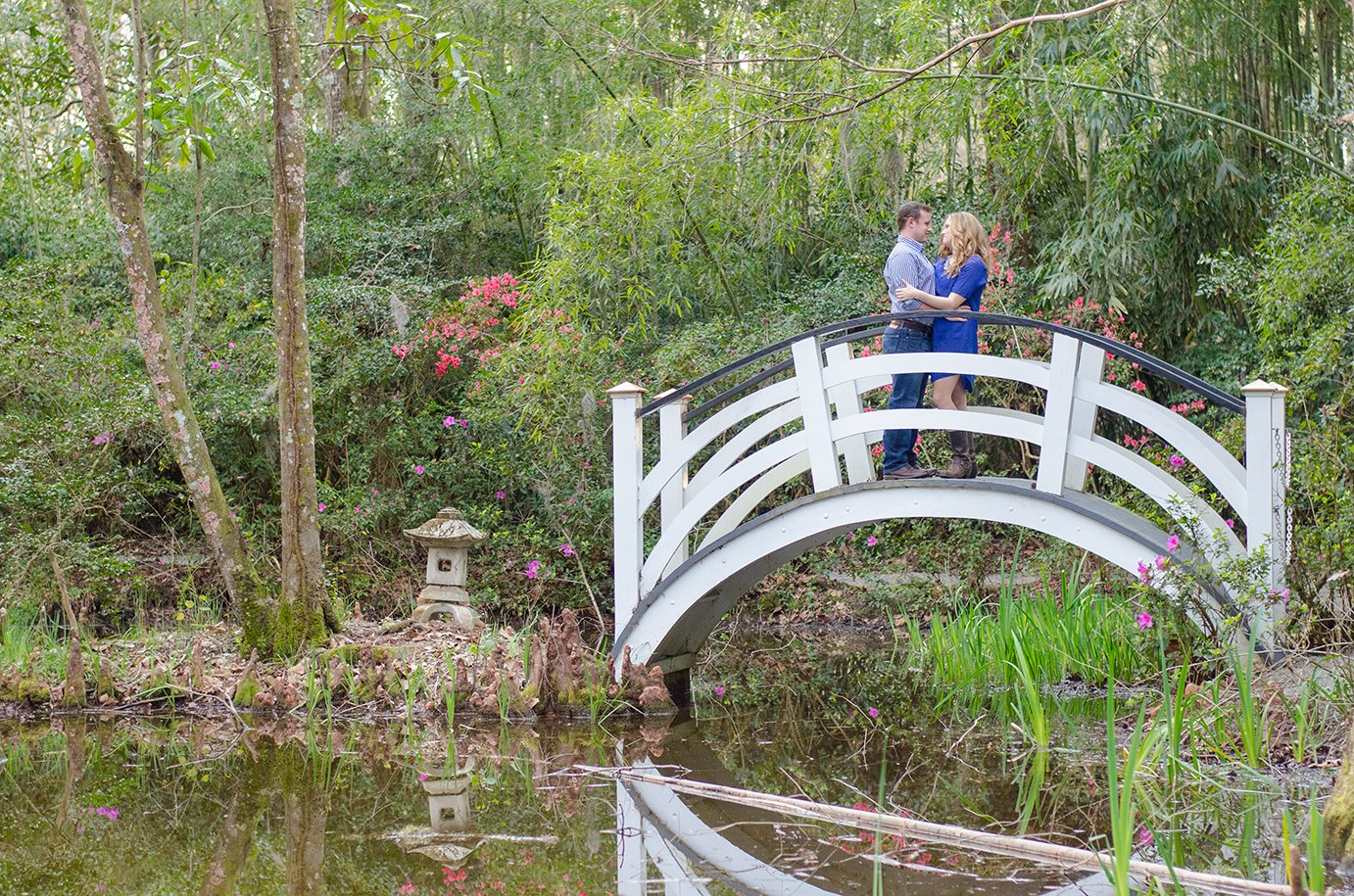 Couple on white bridge at Magnolia Plantation in Charleston, SC during their engagement photography session