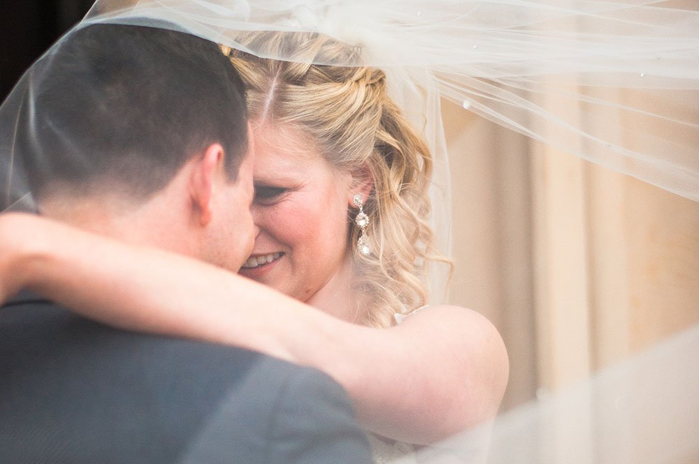 Bride and Groom under bride's veil captured by Charleston wedding photographer Photography By Cameron