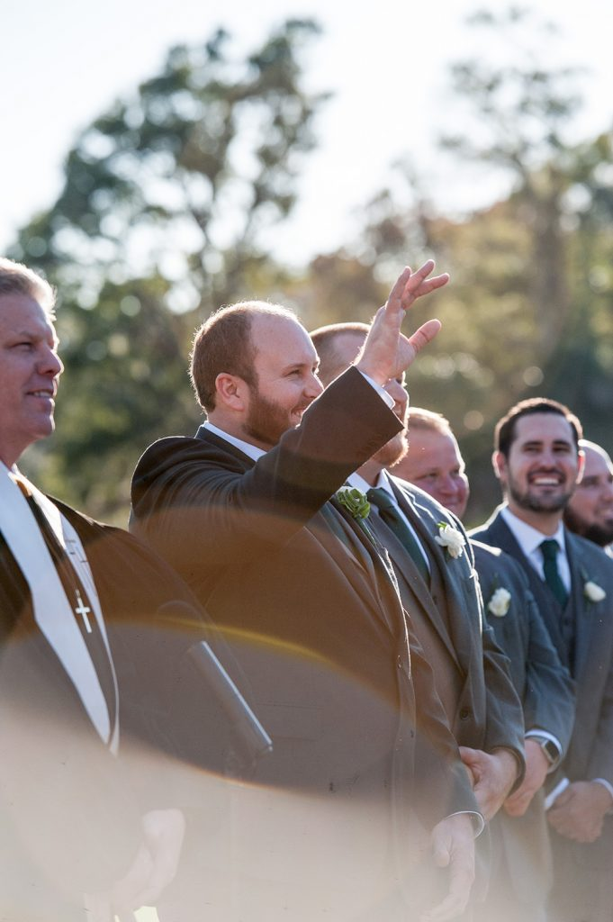 Groom waiving at bride during wedding ceremony at Dataw Island Club near Beaufort SC
