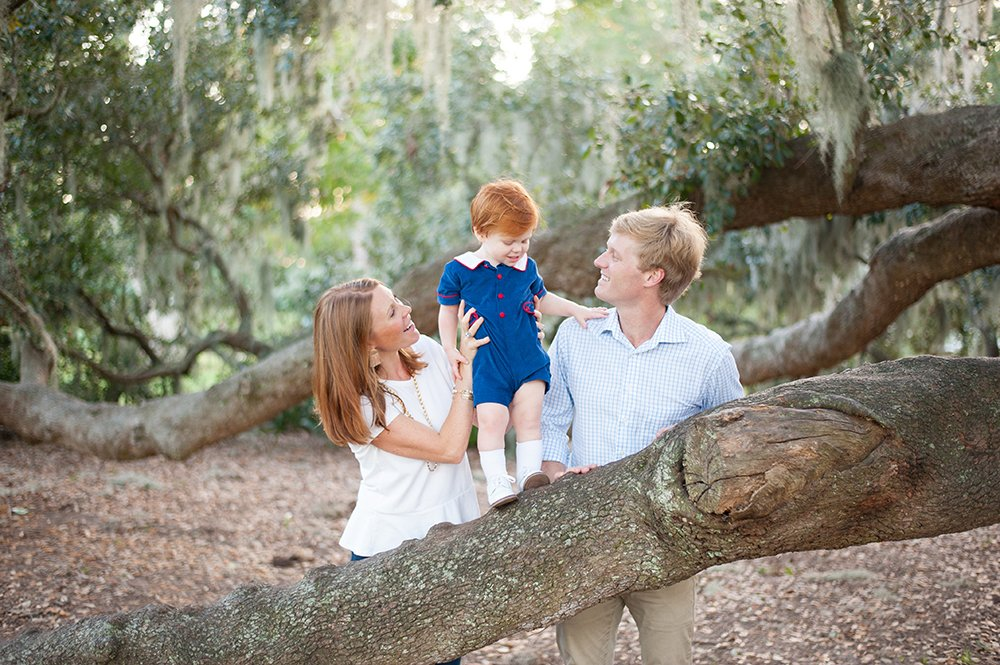 Hampton Park family photos - child stands on tree branch with mom and dad