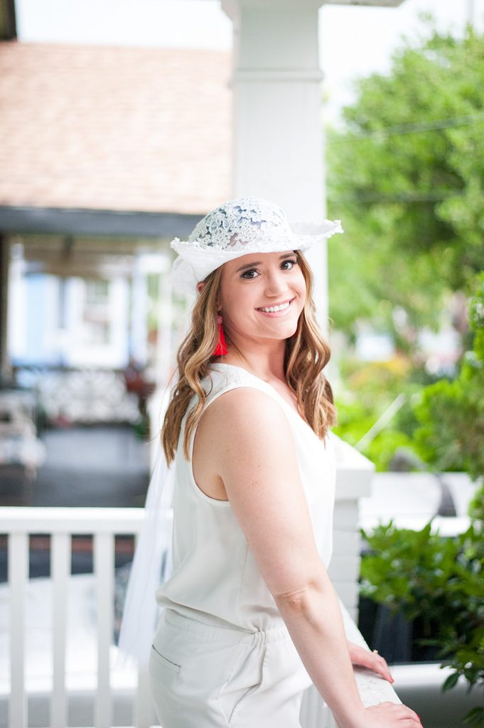 bride in bridal hat on porch during downtown Charleston bachelorette photos