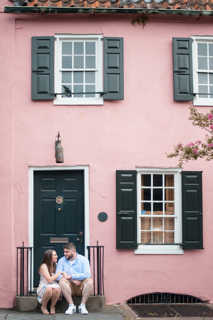 engagement photos in front of the pink house in downtown Charleston, SC