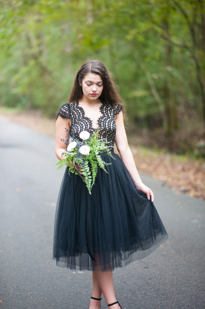 Girl in black lace dress and tulle skirt holding bouquet. Halloween inspired photo shoot in Charleston