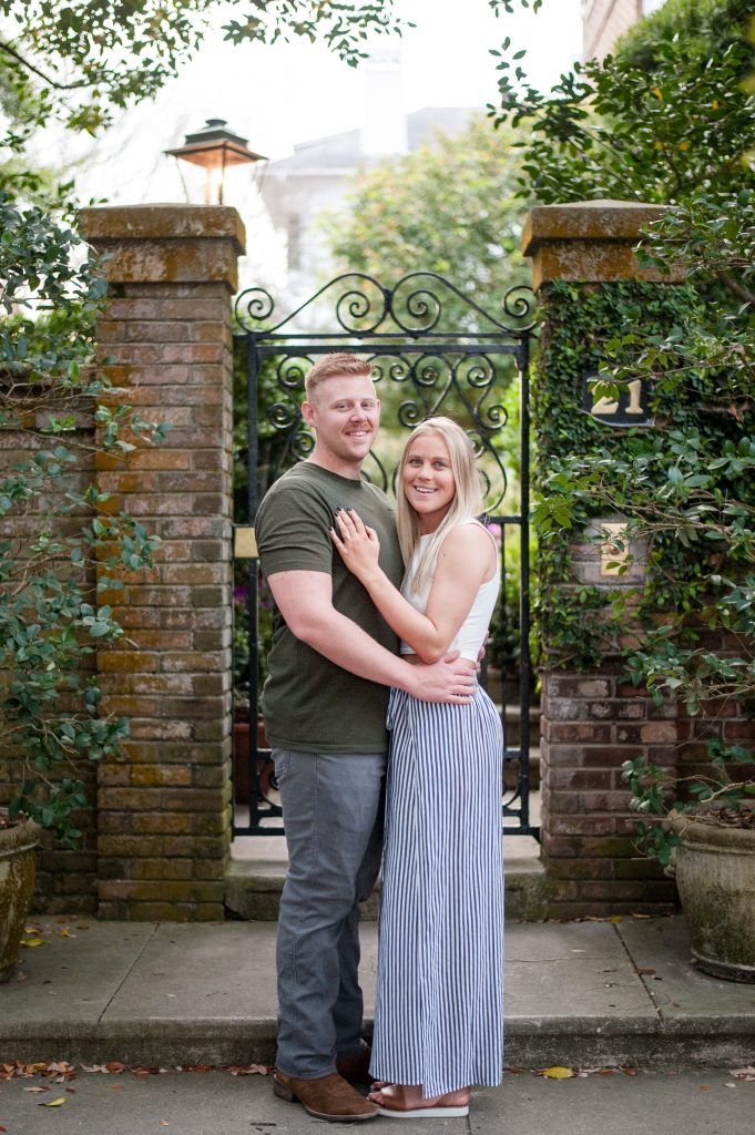 Couple smiling in front of brick and iron gate in downtown Charleston during engagement session