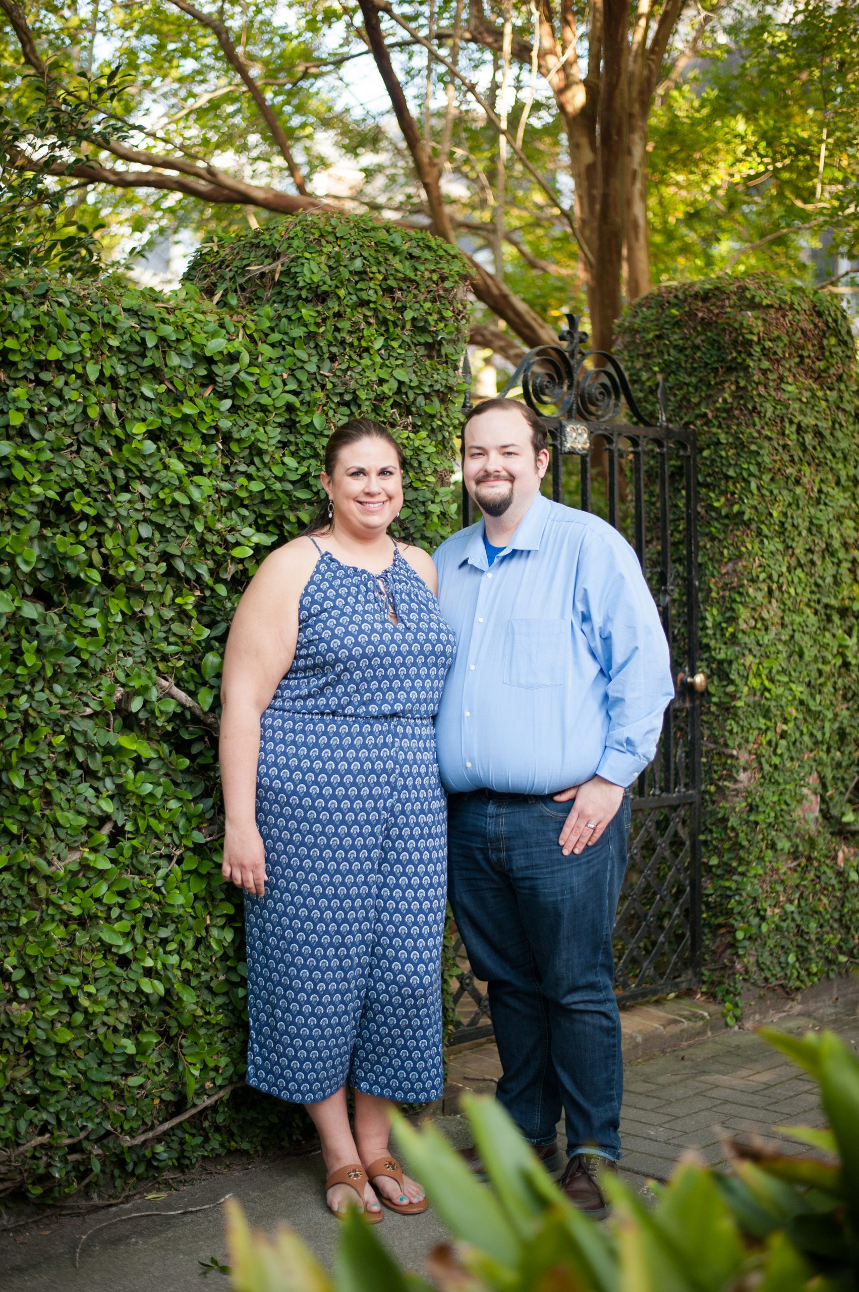 couple standing in front of ivy covered wall during downtown charleston anniversary photos