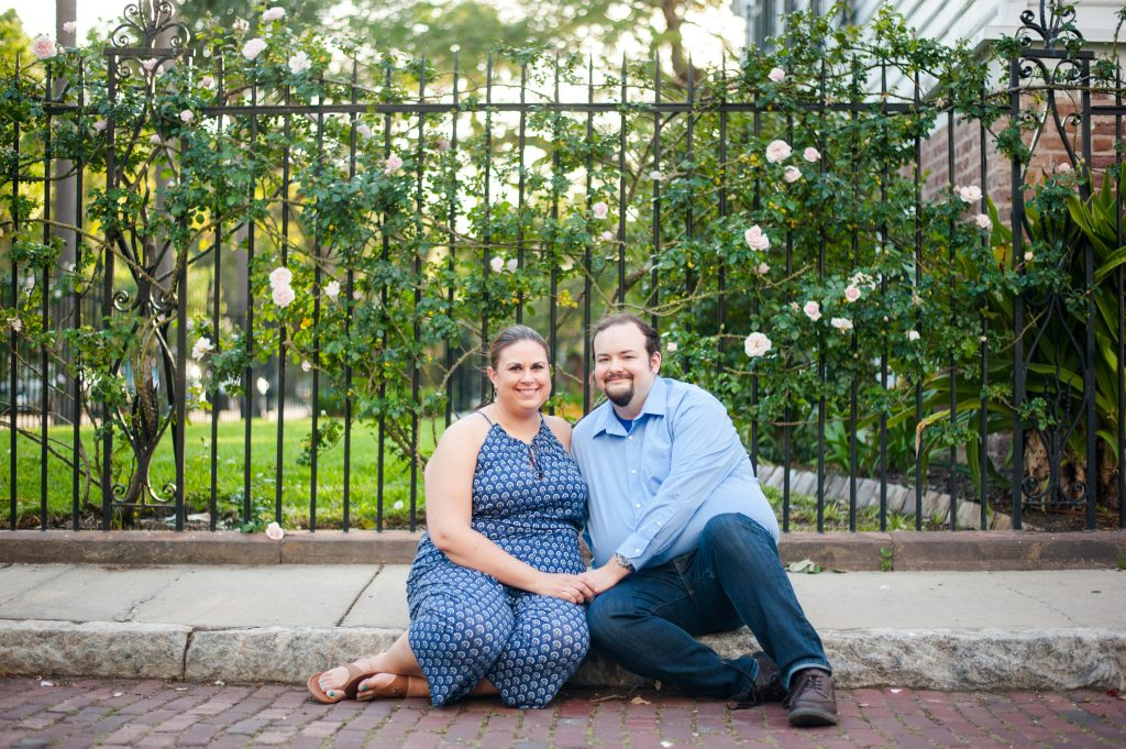 couple sits on sidewalk in front of wrought iron fence in downtown Charleston anniversary photos