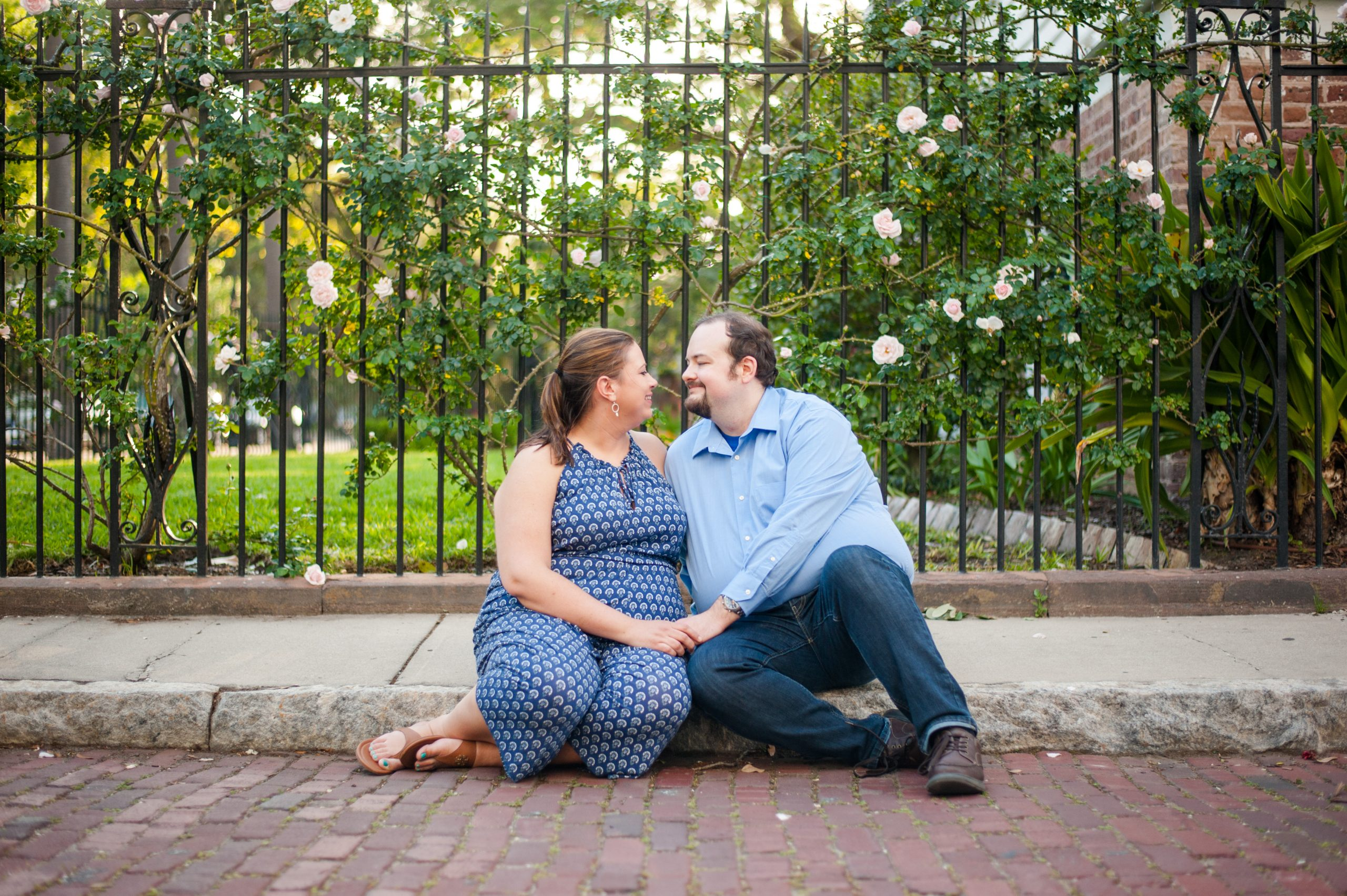couple sitting in front of wrought iron fence Downtown Charleston