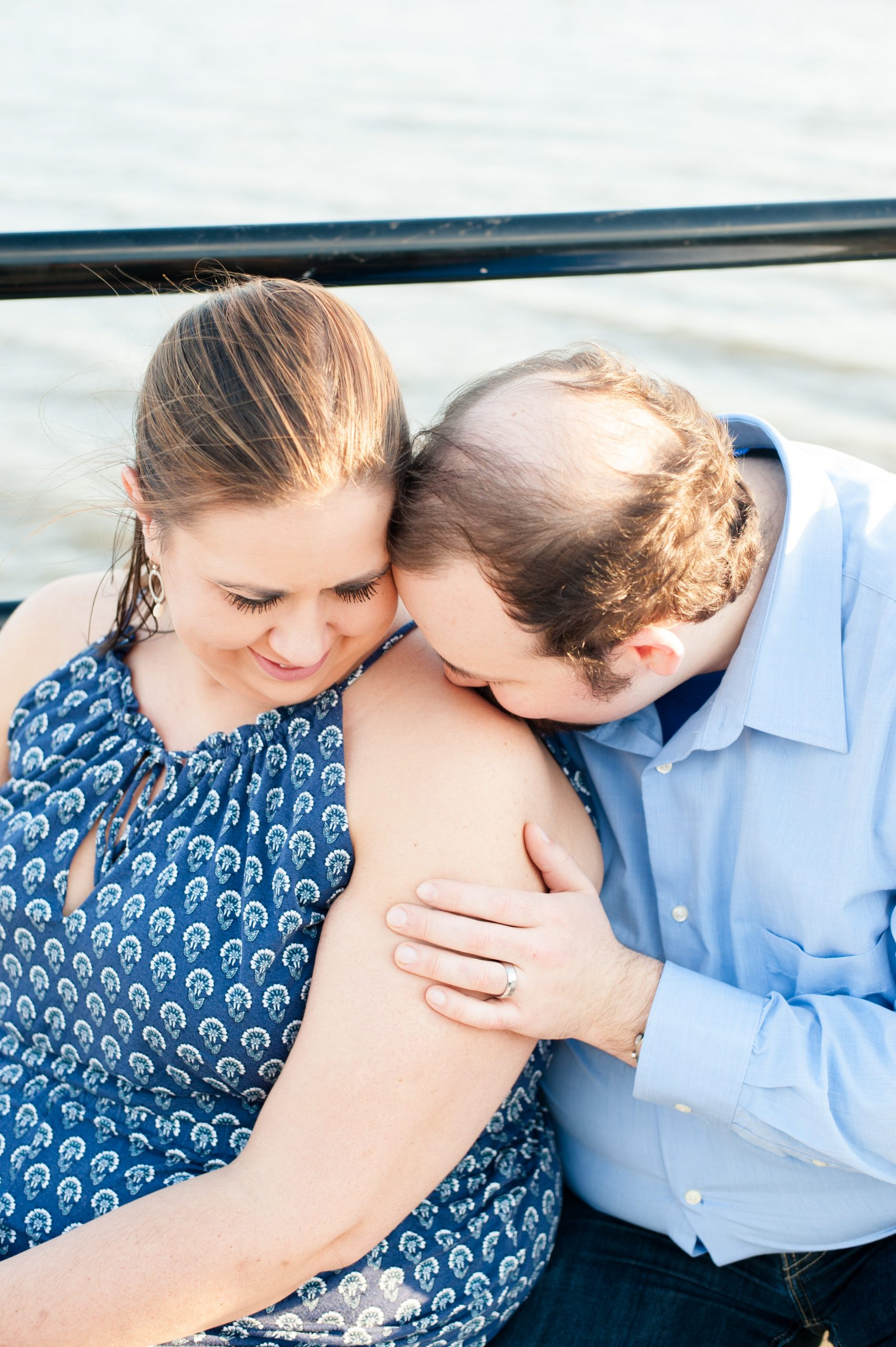 man kisses wife's shoulder during anniversary photo session