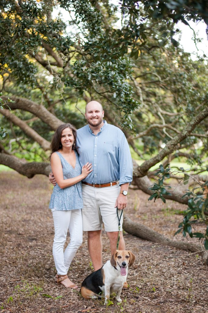 Couple posing with their dog under a tree at Hampton Park family session