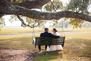 couple sits in swing at Cypress Trees Plantation Wedding