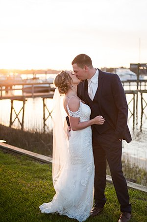 Bride and groom kiss beside dock at The Island House wedding