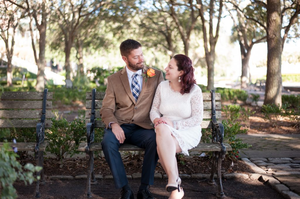 bride and groom sitting on bench at waterfront park in Charleston, SC