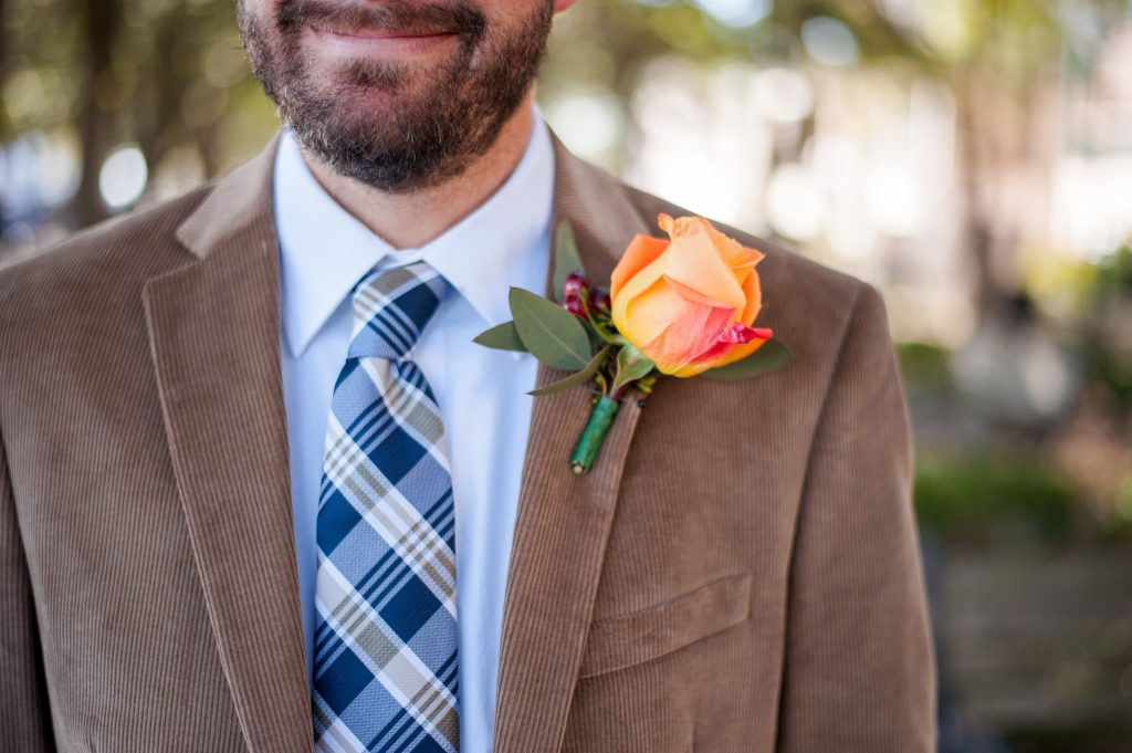 groom with orange rose boutonniere