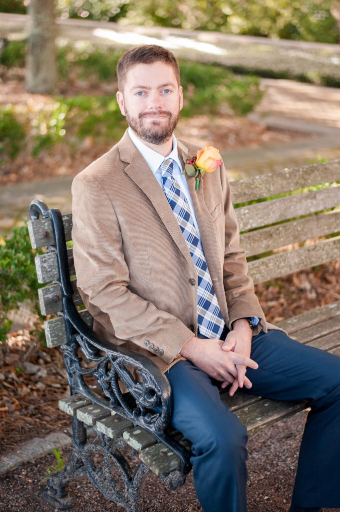Groom sitting on bench in Waterfront Park in Charleston, SC