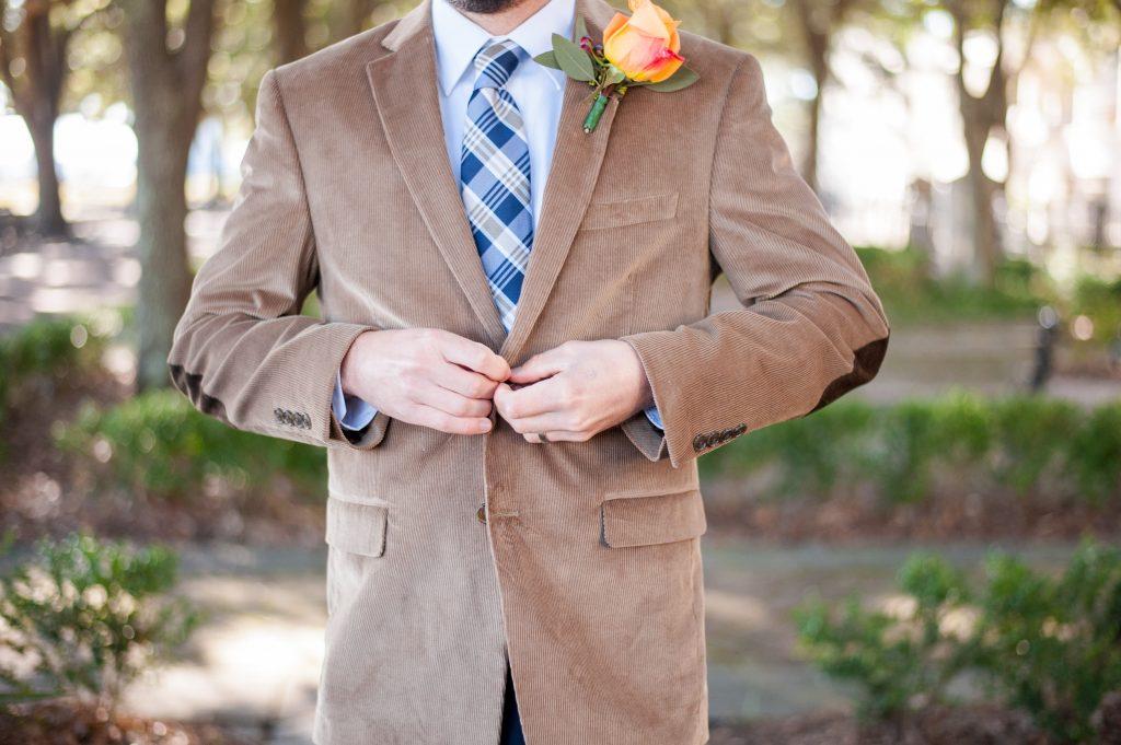 groom buttoning brown coat