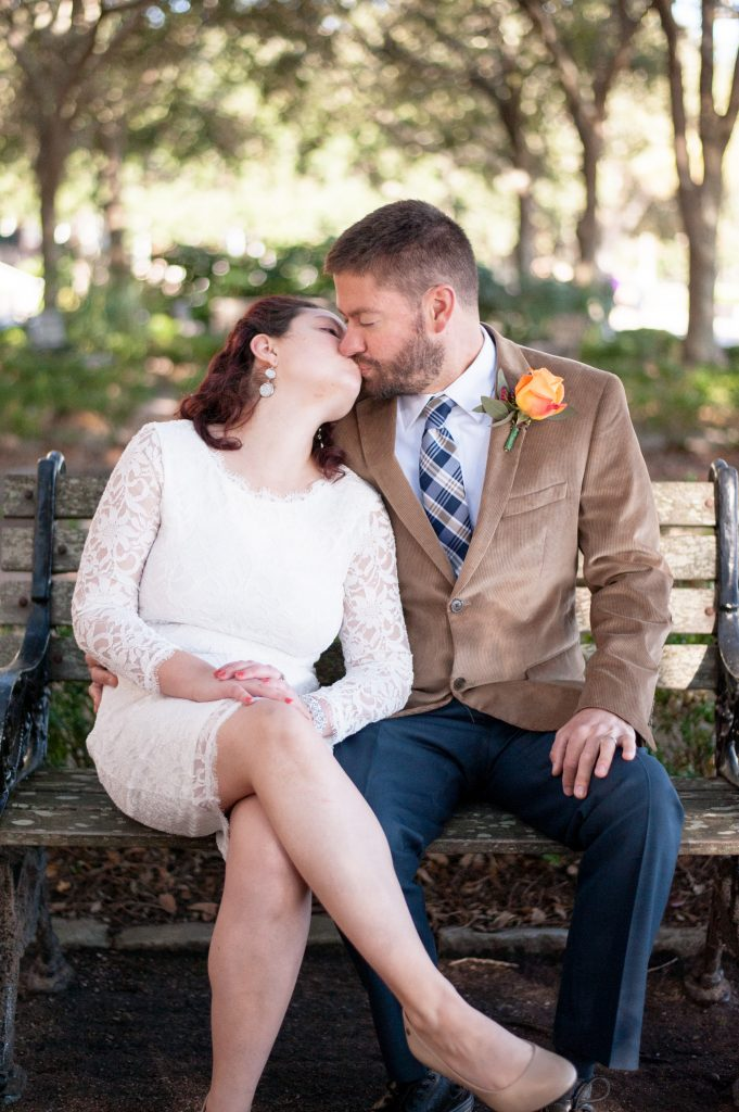 bride and groom sitting on bench kissing after Waterfront Park elopement in Charleston, SC