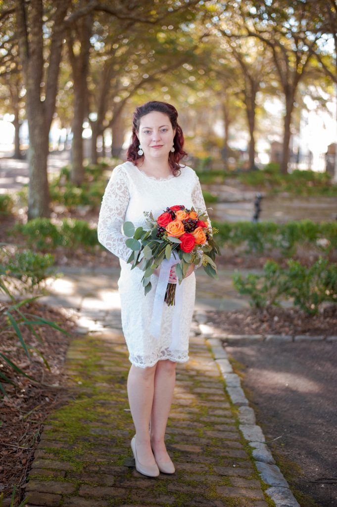 bride standing in waterfront park in Charleston, SC wearing short white dress