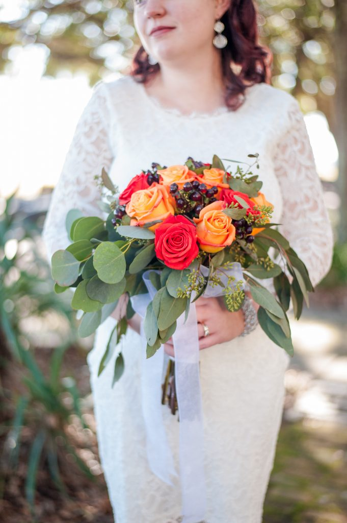 Bride's fall wedding bouquet with red and orange roses