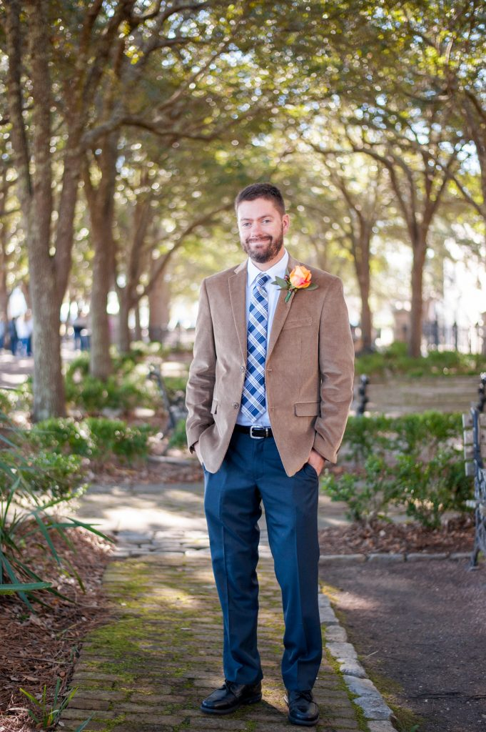 groom standing in waterfront park in Charleston, SC wearing brown jacket and blue checkered tie
