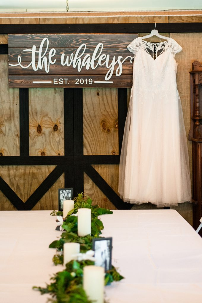 wedding dress hanging in barn beside personalized wedding sign