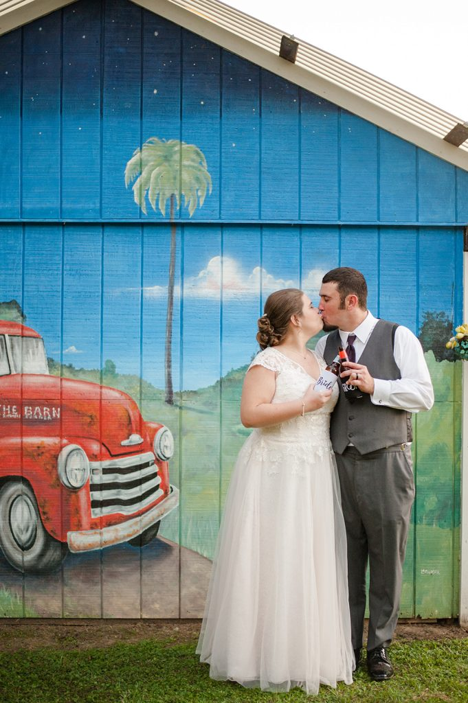 bride and groom in front of mural at the Barn on Summers Drive in Charleston, SC