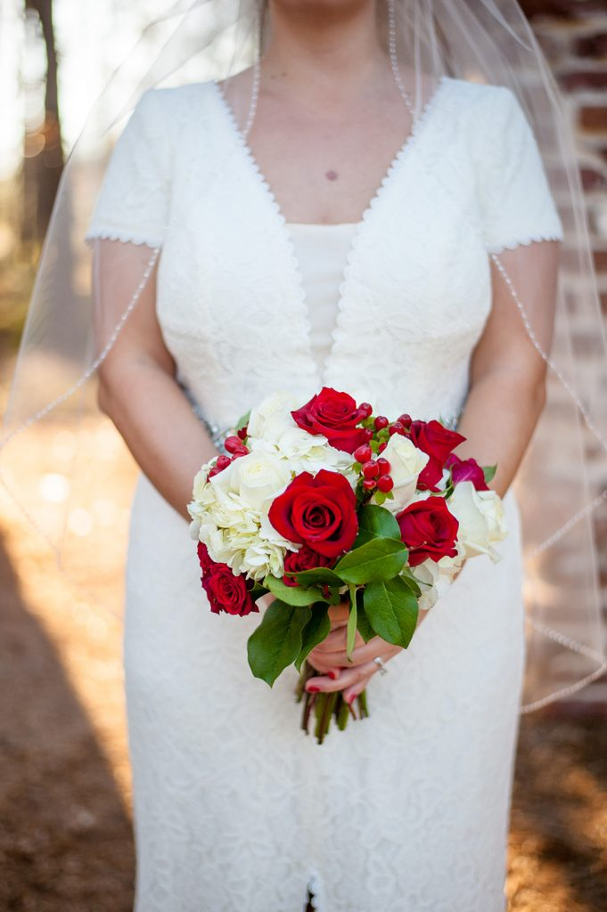 Bride holding red rose wedding bouquet at Charleston wedding