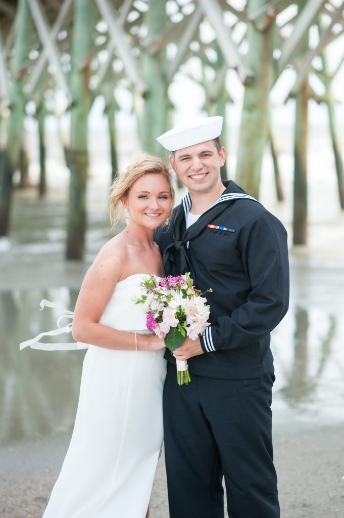 bride and groom standing under Folly Beach pier - Folly Beach elopement