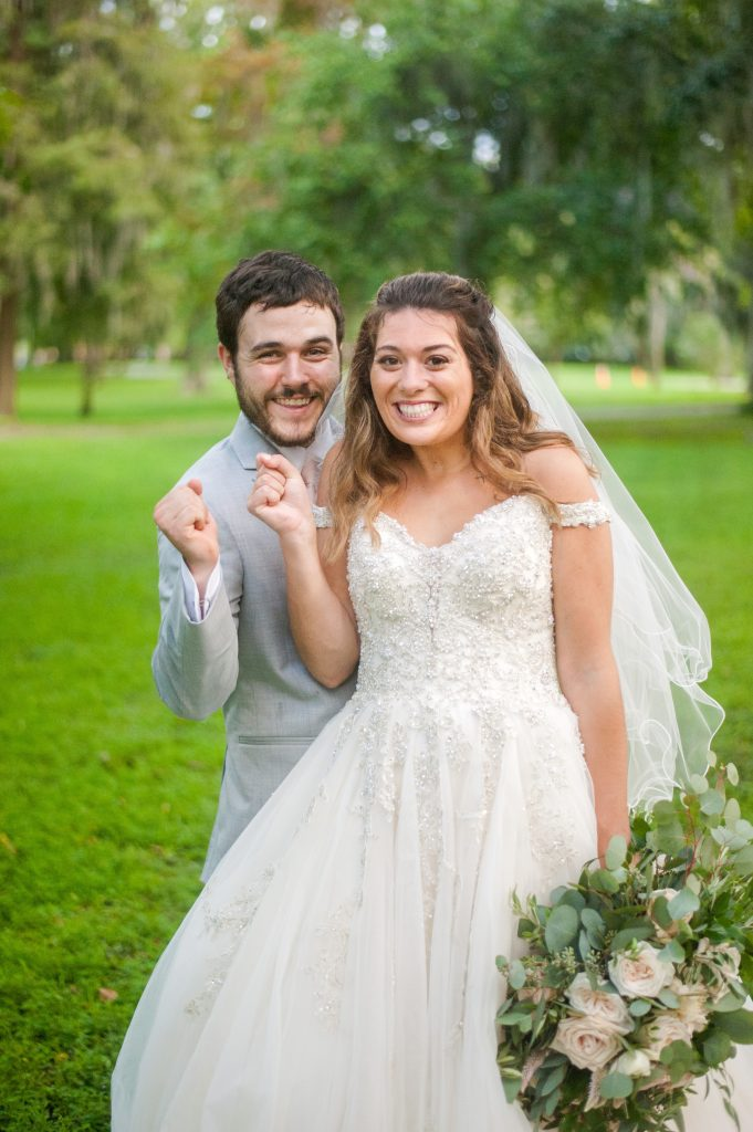 bride and groom cheering in Forsyth Park