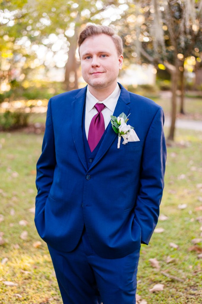 groom wearing classic blue suit in Forsyth Park in Savannah, GA