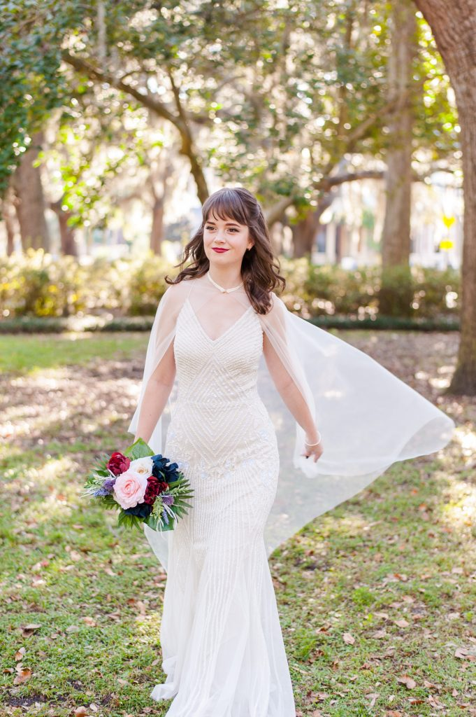bride wearing bridal cape in Forsyth Park in Savannah, GA