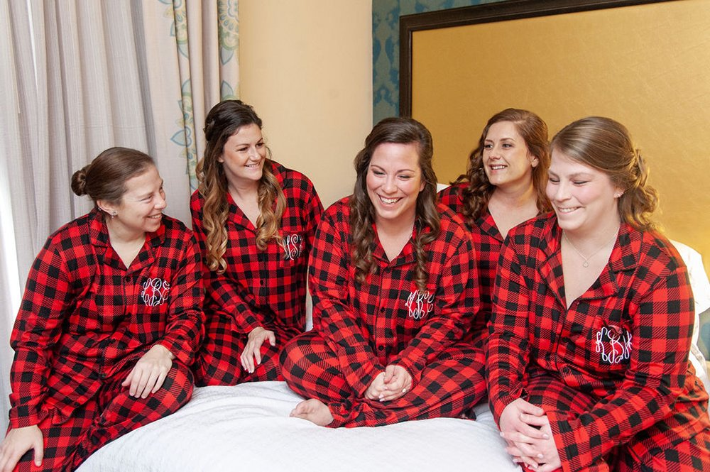 bride and bridesmaids in buffalo plaid pjs before wedding