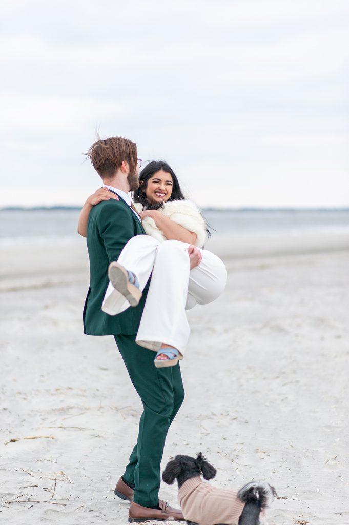 groom carrying bride on Folly Beach