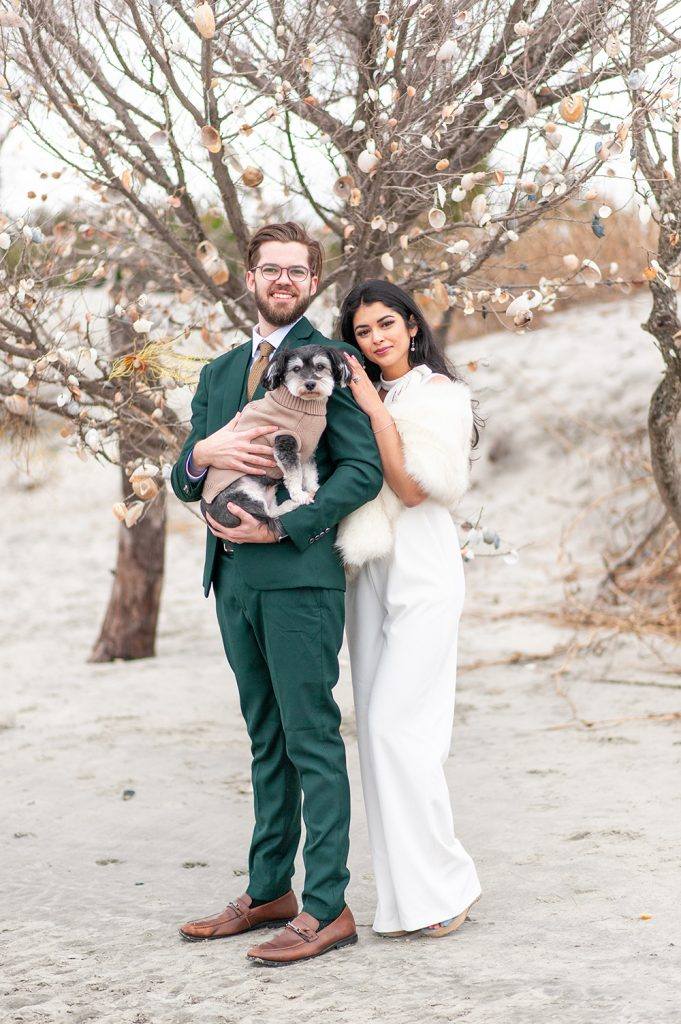 bride and groom holding dog standing in front of seashell covered tree on Folly Beach in Charleston, SC
