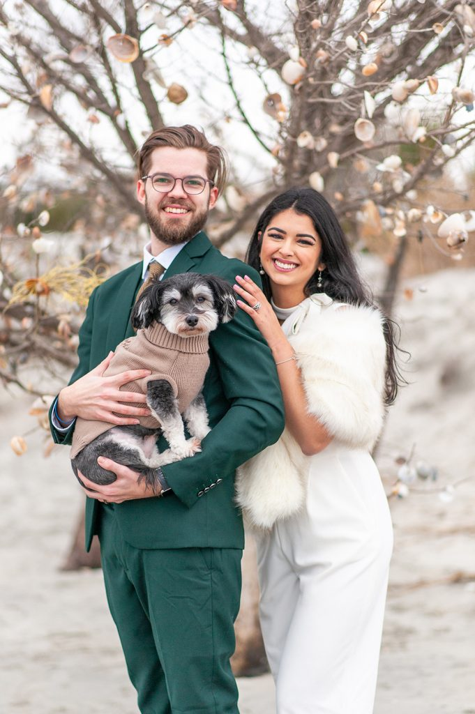 bride and groom holding small dog on Folly Beach after secret elopement