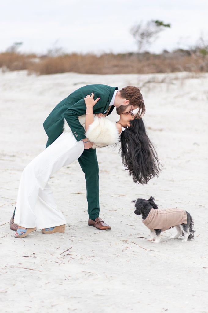 groom dips bride on the beach