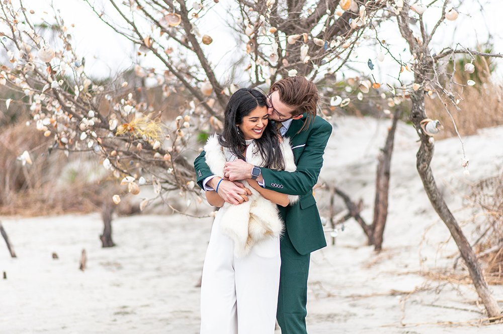 bride and groom hugging on Folly Beach in front of seashell covered tree