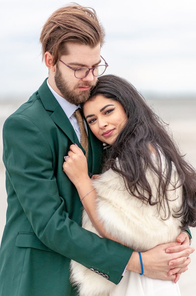 bride in white fur and groom in green suit on Folly Beach