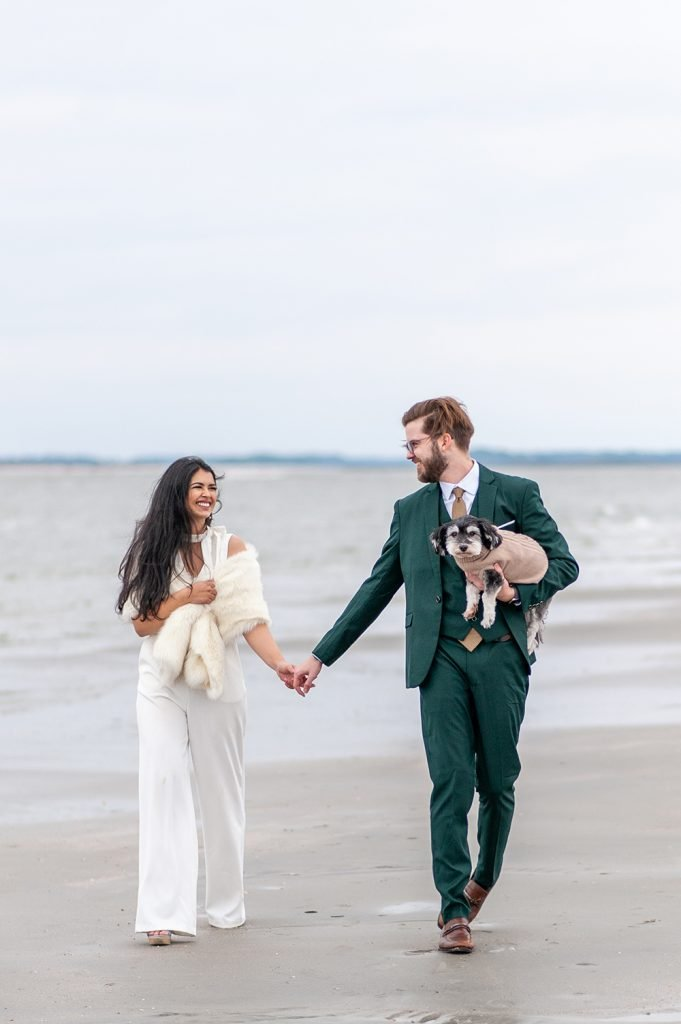 bride and groom walk down Folly beach with dog after Charleston elopement