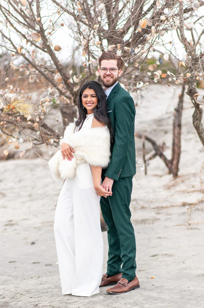 bride and groom in front of seashell covered tree on Folly Beach