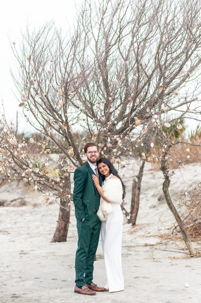 Bride and groom stand in front of seashell covered tree on Folly Beach in Charleston, SC