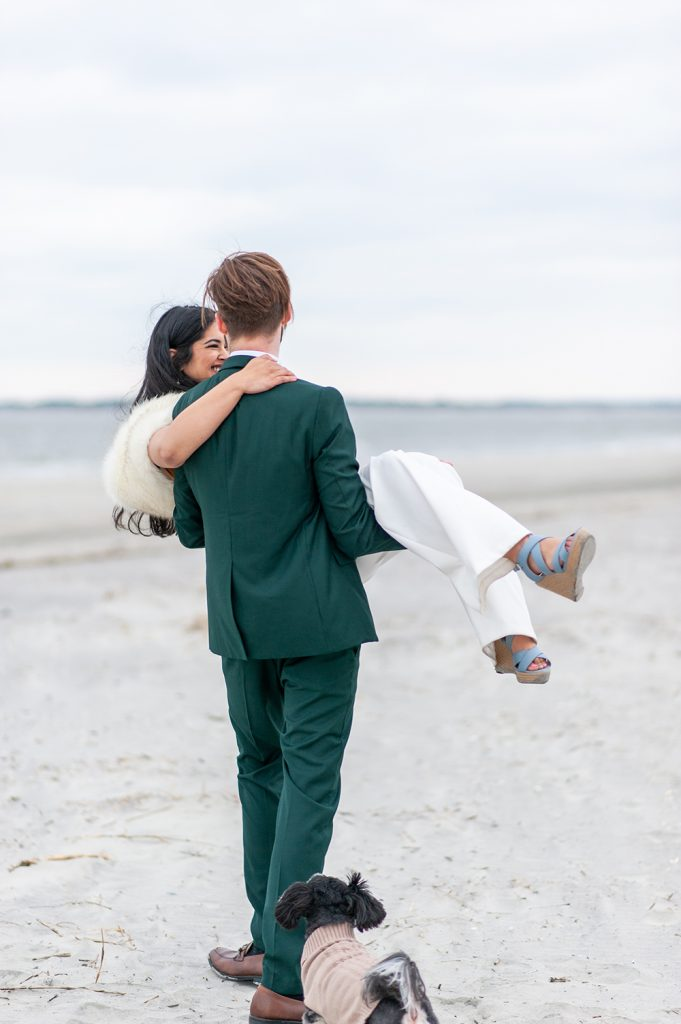 groom carrying bride down the beach after elopement on Folly Beach in Charleston, SC