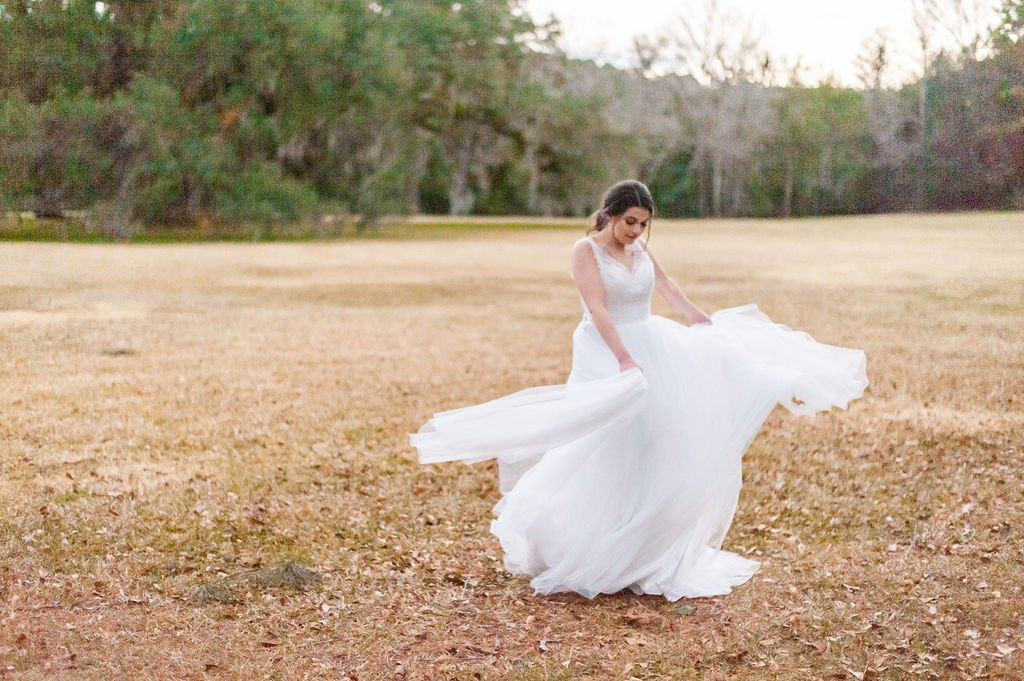 Bride twirling in wedding gown at Runnymede Plantation in Charleston, SC