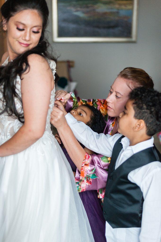 Bride getting zipped into wedding dress at Hotel Bennett