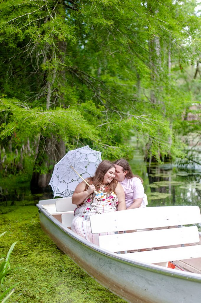 The Notebook inspired Cypress Gardens engagement photos with couple in row boat with parasol