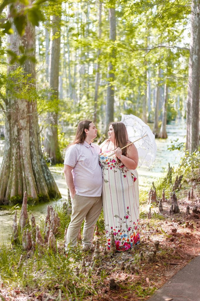 The Notebook inspired Cypress Gardens engagement photos with couple beside swamp with parasol