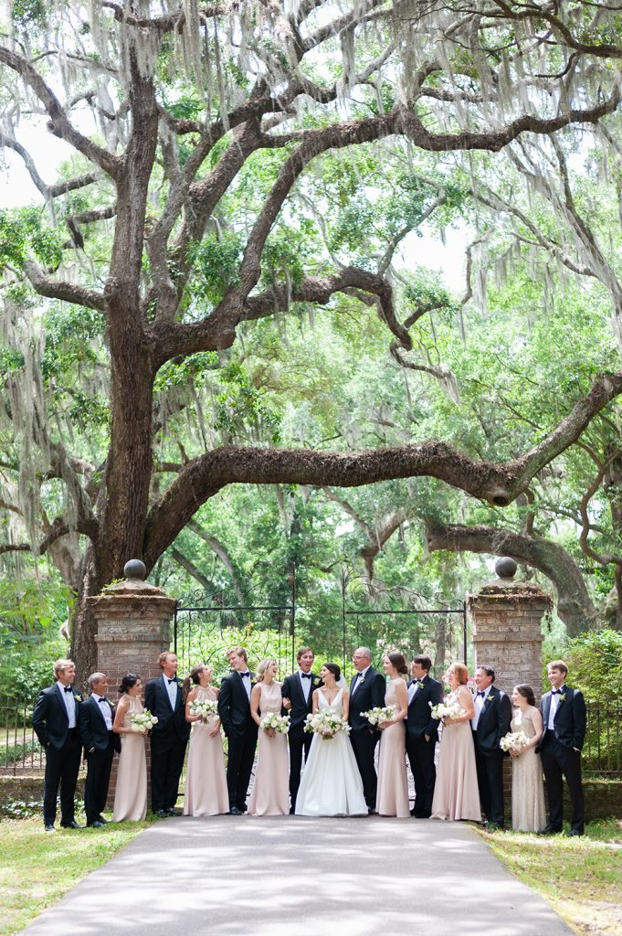 Wedding party portrait in front of wrought iron gate at Legare Waring House
