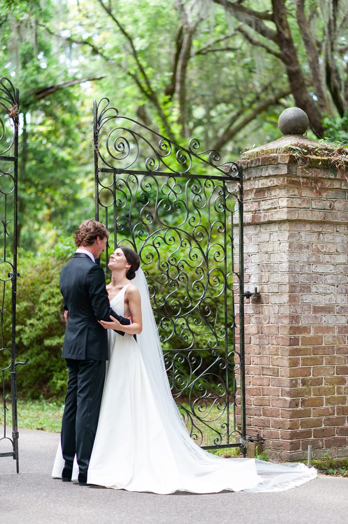 bride and groom portrait beside wrought iron gate at Legare Waring House