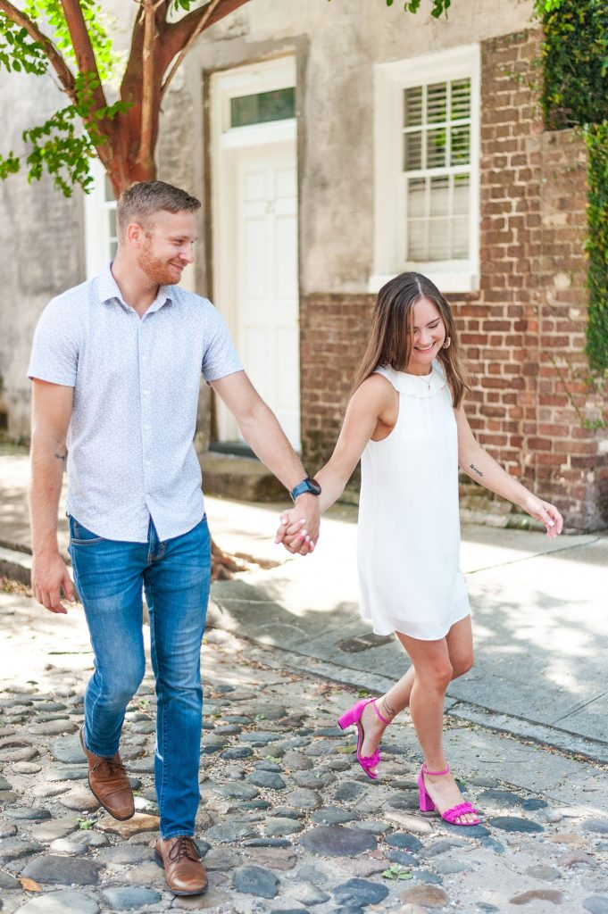 couple walking on cobblestone in downtown Charleston engagement photos
