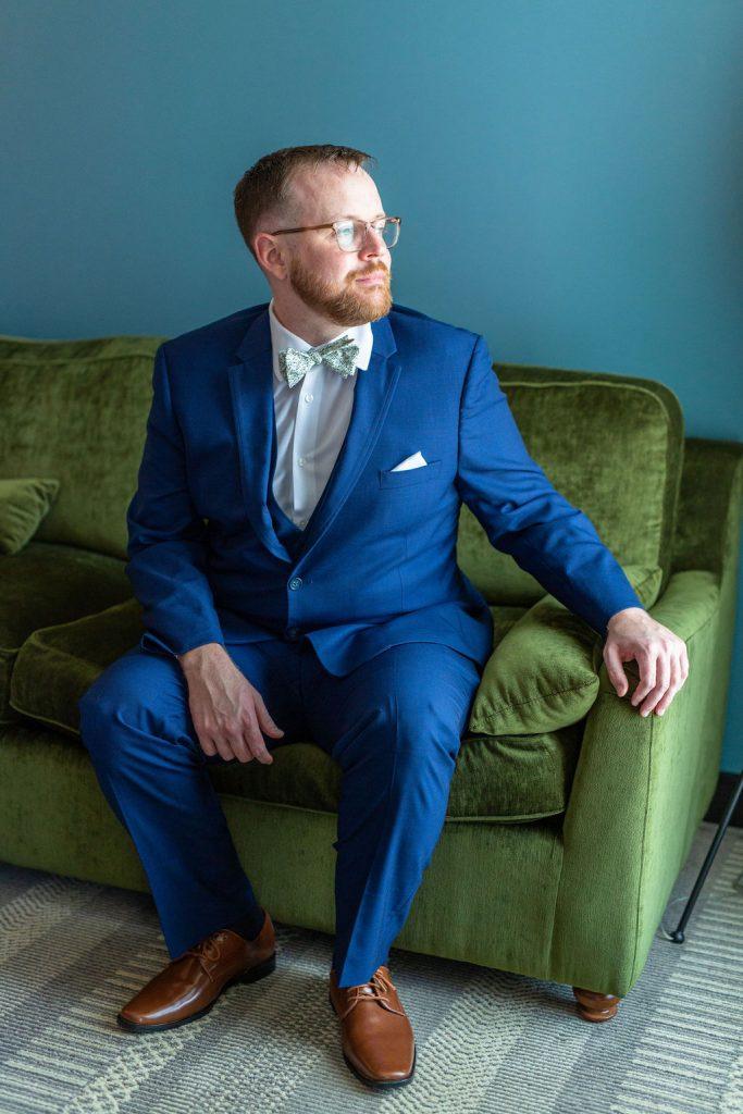 Groom in blue suit sitting at Hotel Emeline